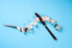 Вилка и нож с сантиметром на голубой предпосылке, диета, здоровый образ жизни стоковое фото rf