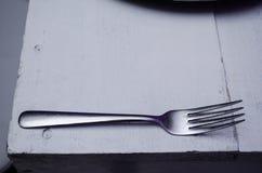 Вилка на белом деревянном столе, красивая предпосылка Chrome для украшая представлений еды стоковая фотография