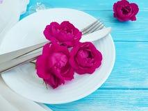 Вилка, нож, плита, датировка концепции розовой годовщины цветка праздничное на голубой деревянной предпосылке, романтичном дизайн стоковые фотографии rf