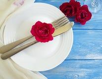 Вилка, нож, плита, датировка концепции розы цветка праздничное на голубой деревянной предпосылке, романтичном дизайне стоковое изображение