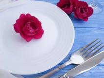 вилка, нож, плита, датировка розы цветка праздничное на голубой деревянной предпосылке, романтичном дизайне стоковое изображение