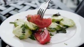 Вилка прокалывает салат на белом конце-вверх плиты, замедленное движение томата и огурца сток-видео