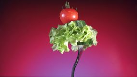 Вилка с свежими красными томатом и огурцом в капельках воды и салата поворачивает красную предпосылку видеоматериал