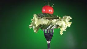 Вилка с свежими красными томатом и огурцом в падениях и салате воды поворачивает зеленую предпосылку акции видеоматериалы