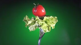 Вилка с свежими томатом и огурцом отрезка красного цвета в капельках воды и салата поворачивает голубую предпосылку сток-видео