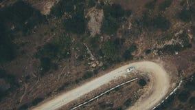 Виллис автомобиля вида с воздуха белый двигая вдоль горы извилистой дороги на летнем дне сток-видео
