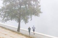 ВИЛЬНЮС, ЛИТВА - 21-ОЕ ОКТЯБРЯ 2018: Соедините бегунов идя для jog в тумане утра берегом реки стоковые изображения rf