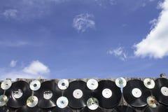Винил и компактный диск привинченные к загородке против предпосылки голубого неба Стоковые Фото