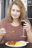 Виновная женщина есть на вынос карри и выпивая вино Стоковые Фотографии RF