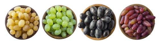 Виноградины в деревянном шаре изолированном на белой предпосылке Голубые, желтые, красные и зеленые виноградины на белой предпосы стоковое изображение