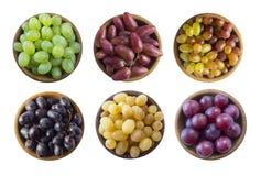 Виноградины в деревянном шаре изолированном на белой предпосылке Желтый, голубой, пинк и зеленый виноградина на белой предпосылке стоковое фото