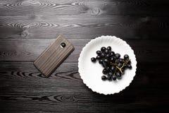 Виноградины в плите на темной деревянной предпосылке стоковое фото