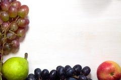 Виноградины, груша и яблоко свежих фруктов на деревянных досках обрамляют предпосылку стоковые фотографии rf