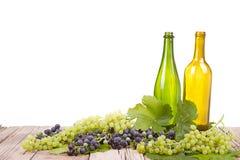 Виноградины и бутылки на деревянной планке стоковые фото