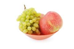 Виноградины и яблоки на плите Стоковое Фото