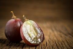 виноградины красные ломтик половинно таблица поля глубины отмелая деревянная стоковое фото rf
