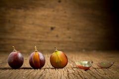 виноградины красные ломтик половинно таблица поля глубины отмелая деревянная стоковые изображения