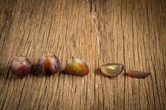 виноградины красные ломтик половинно таблица поля глубины отмелая деревянная стоковое изображение