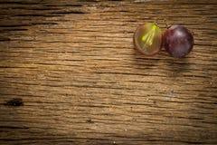 виноградины красные ломтик половинно таблица поля глубины отмелая деревянная стоковое изображение rf