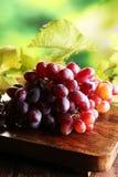 Виноградины на листьях деревянного стола и виноградины Здоровые виноградины вина свежих фруктов Стоковые Фото