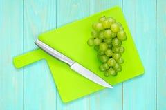 Виноградины с ножом на разделочной доске Стоковые Изображения