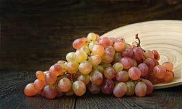 Виноградины зрелая связка винограда лежа на круглой деревянной плите на темной предпосылке стоковое фото