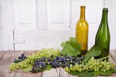 Виноградины и бутылки на деревянной планке Стоковое Изображение RF