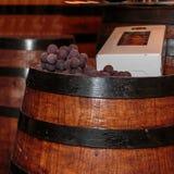 Виноградины и коробка бутылки на бочонке точного большого вина деревянном Стоковое Изображение