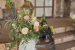 Виноградины на вазе около цветков и бутылки лозы Стоковое фото RF