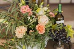 Виноградины на вазе около цветков и бутылки лозы Стоковое Изображение