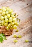 Виноградины с листьями в корзине на деревянной доске Стоковая Фотография RF