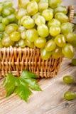 Виноградины с листьями в корзине на деревянной доске Стоковое Фото