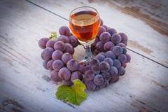 Виноградины с лист и бокал вина на деревянном столе в саде Стоковая Фотография RF