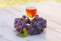 Виноградины с лист и бокал вина на деревянном столе в саде Стоковое Изображение