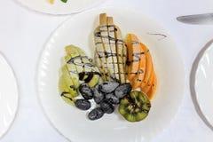 Виноградины, яблоко, груша, апельсин, киви отрезанный и предусматриванный шоколадом и отбензиниванием сахара Стоковое фото RF