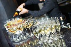 Вино бармена кельнера лить на партии стоковая фотография