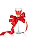 Вино в рюмке и красном смычке подарка сатинировки,   Стоковая Фотография RF