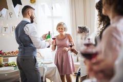 Вино гостей человека лить на крытом дне рождения семьи стоковое изображение rf