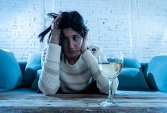 Вино грустной, несчастной, беспомощной женщины выпивая самостоятельно дома Человеческие эмоции, депрессия и алкоголизм стоковое фото rf