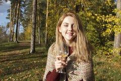 Вино девушки выпивая в лесе осени Стоковая Фотография RF