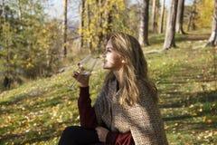 Вино девушки выпивая в лесе осени Стоковые Фотографии RF