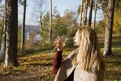 Вино девушки выпивая в лесе осени Стоковое Фото