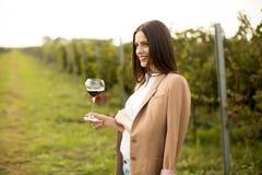 Вино дегустации молодой женщины в винограднике Стоковые Фотографии RF
