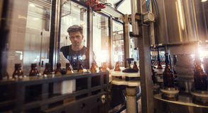 Винодел наблюдая процесс пива разливая по бутылкам Стоковое Фото