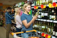 Вино женщины покупая в супермаркете Стоковые Фотографии RF