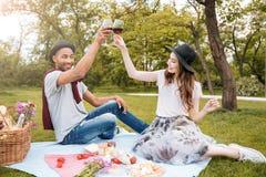Вино жизнерадостных пар выпивая на пикнике Стоковое Фото
