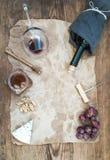 Вино и закуска установили с космосом экземпляра в центре Стекло красного вина, бутылки, corkscrewer, голубого сыра, виноградин, м Стоковые Фотографии RF