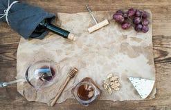 Вино и закуска установили с космосом экземпляра в центре Стекло красного вина, бутылки, corkscrewer, голубого сыра, виноградин, м Стоковые Фото