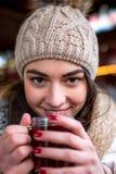Вино кефали белокурого питья женщины теплое на рождественской ярмарке Стоковое фото RF