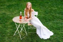 Вино красивой женщины выпивая в кафе outdoors Портрет молодой белокурой красоты в виноградниках имея потеху, наслаждаясь a Стоковое фото RF